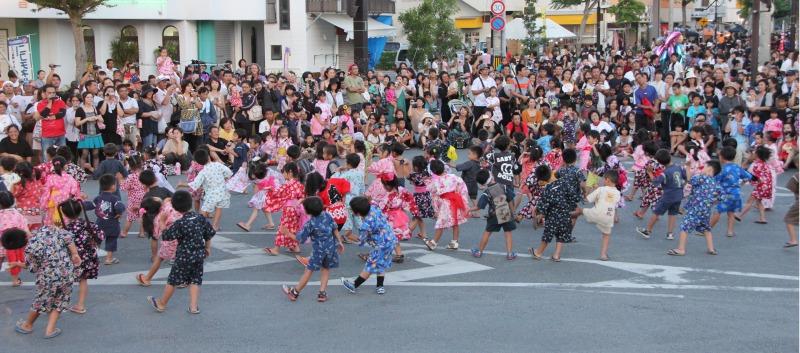 大勢の観客を前に元気な踊りを披露する子どもたち=20日、市場前交差点