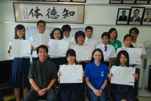 川満校長(手前左)が準1級に合格した伊志嶺百々子さん(同左から2人目)らの頑張りをたたえた=24日、宮古高校