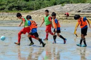 まだ水が残る干潟でボールを追う少年サッカーの子どもたち