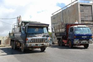 畑へのかん水のためトラックがひっきりなしに出入りし給水している=30日、宮古製糖城辺工場