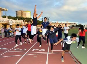10時間走を達成し、跳び上がってゴールする生徒たち。喜びを全身で表現した=17日、市陸上競技場