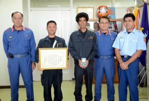消火活動に協力したとして感謝状を受けた大番運送の寄川代表(左から2人目)と前泊さん(中央)=20日、宮古島市消防本部