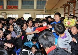 子供たちに握手をせがまれる大儀見さん(右)=17日、平良第一小学校