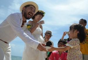 南さん夫婦は女の子から結婚指輪を受け取り、互いにはめて永遠の愛を誓った=28日、来間島のムスヌン浜