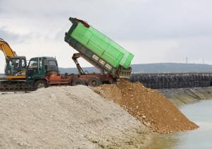 積載した土砂を埋め立て現場に下ろすダンプカー=25日、平良港・漲水地区