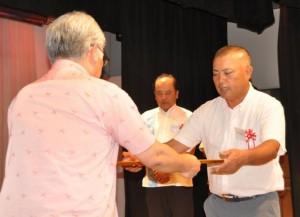 宮城理県土木建築部長(左)から優良建設業者として表彰される宮里社長(右)=24日、那覇市内のホテル