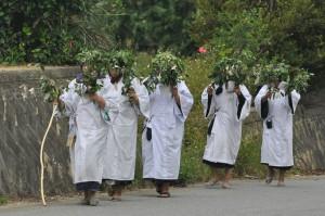 草の冠を頭に載せ清楚な白い服姿で集落内を通るニガインマたち