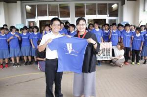 津嘉山生徒会長(手前左)にTシャツを手渡す趙理事長(同右)=5日、下地中学校
