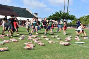 「お菓子ひろい」で一目散に走る笑顔の子どもたち=11日、西原町民陸上競技場