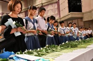 参列した生徒たちが献花でみ霊を慰めた=23日、マティダ市民劇場