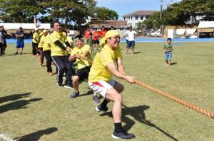 気合いの表情で綱を引っ張る参加者=10日、浦添市陸上競技場