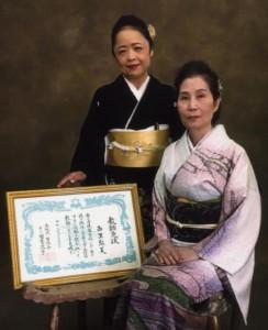 教師免状を取得し國吉家元(手前)と記念撮影する西里さん(提供写真)