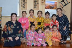 師匠の神里さん(写真左)と舞踊を習っている子どもたち。右は大人に教えている母和子さん