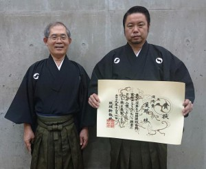 合格し笑顔の漢那さん(右)と指導に当たった久貝哲雄さん(提供写真)