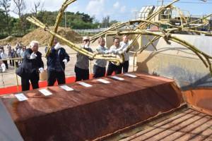 安村社長(左から3人目)らによるベルトコンベヤーへのキビ投入で本格操業が開始した=19日、宮古製糖伊良部工場