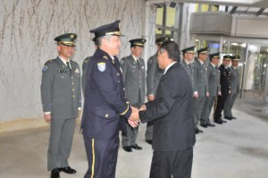 栗田群長(手前左)らを出迎え、握手する垣花副会長(同右)=23日、宮古空港