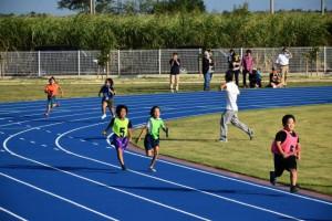 新しいグラウンドで小中合同縦割りチームリレーをする児童生徒たち=10月28日、多良間中グラウンド