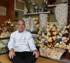 自慢の貝殻細工作品と一緒に記念撮影に応じた友利弘一さん=平良高野の友利さん宅