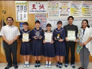 松本校長(左)に報告するボランティア委員会のメンバーと湧川教諭(右)=多良間中校長室