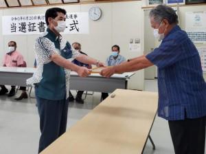 3期目当選を果たした伊良皆氏(左)に当選証書を付与する長崎委員長=22日、村役場