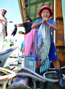 大物カツオ(トビダイ)を持ち上げる子供たちからは「大きい」「重い」などの感想が聞かれた=29日、佐良浜漁港