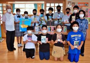 本を寄贈した佐和田さん(右端)=21日、伊良部島小・中学校